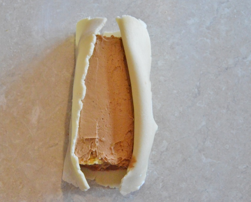 """(E) Lift up the marzipan """"flaps"""", using a little more buttercream to adhere to the sponges if needed"""