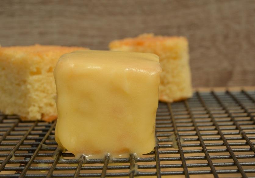 Runny buttercream poured over frozen cake